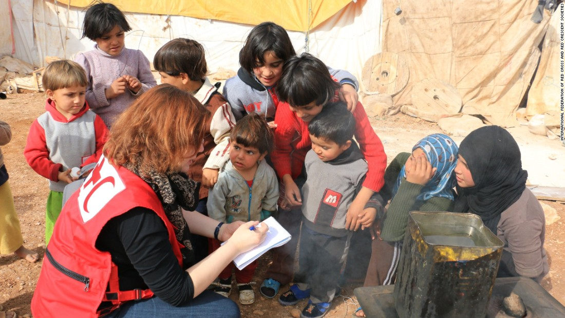 A Red Crescent volunteer speaks with Syrian refugees in Jordan. The International Federation of the Red Cross and Red Crescent Societies help 3.7 million Syrians each month. About 3,000 IFRC volunteers are working with the Syrian crisis and  47 IFRC volunteers have died in the line of duty.
