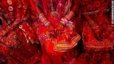 Indian brides from impoverished families, dressed in wedding finery, wait for their grooms to arrive during a mass marriage ceremony in New Delhi, India, Friday, Feb. 20, 2015.