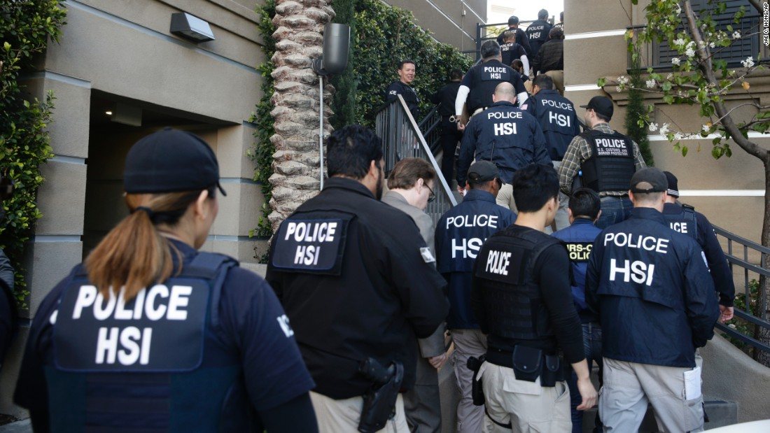 "Federal agents enter an upscale apartment complex on Tuesday, March 3, in Irvine, California. More than three dozen ""maternity hotels"" were raided in Southern California, where foreign women give birth, allegedly for the sole purpose of having a U.S.-citizen baby, authorities said."