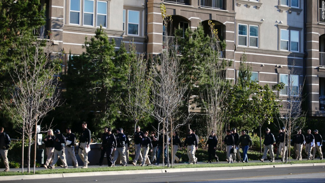 Federal agents walk by an upscale apartment complex, where authorities say a birth tourism business charged pregnant women $50,000 for lodging, food and transportation.