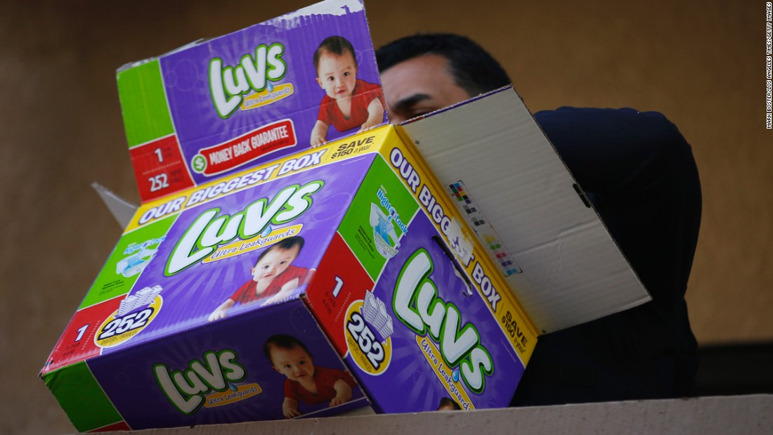 A federal agent looks through a disposable diaper box while serving warrants at an apartment complex during an ongoing investigation of alleged birth tourism centers.
