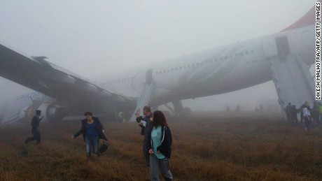 Passengers walk away from a Turkish Airlines plane after it skidded off the runway while landing at Kathmandu airport in the Nepalese capital Kathmandu on March 4, 2015. Aviation officials said no one on board was injured, although one witness described how terrified passengers leapt from their seats as the cabin filled with smoke after the plane skidded to a halt. AFP PHOTO / Dikesh Malhotra        (Photo credit should read Dikesh Malhotra/AFP/Getty Images)