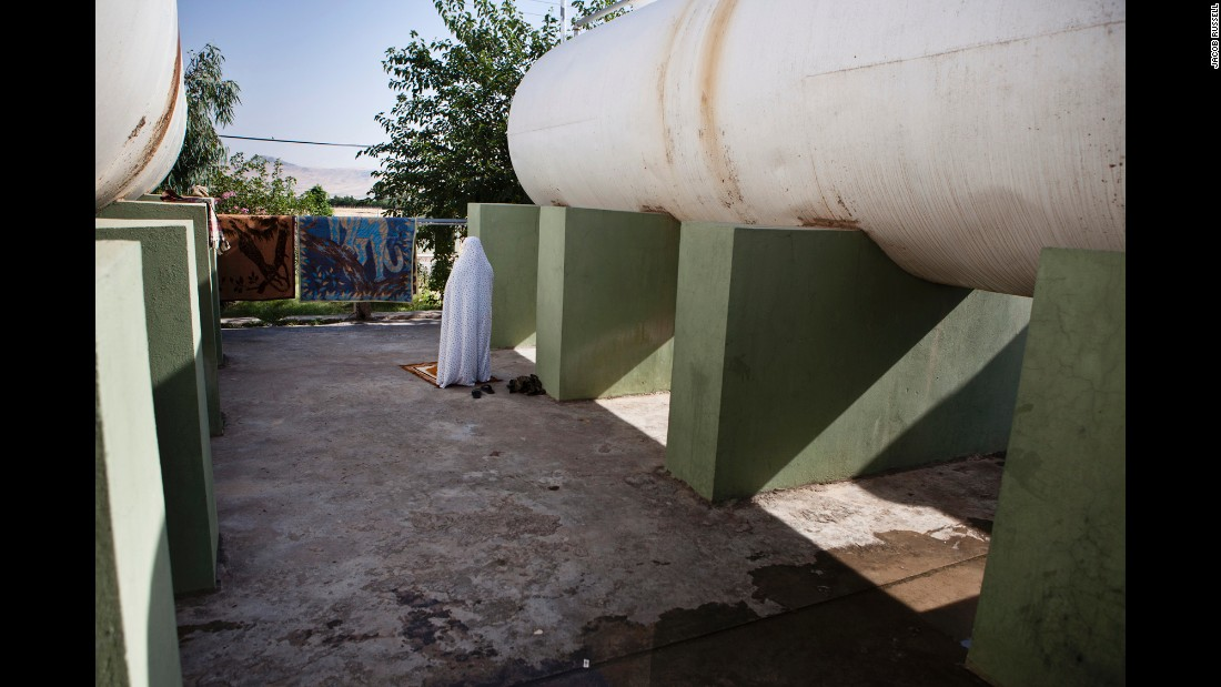 A female Peshmerga prays near water tanks at the base in Sulaymaniyah.