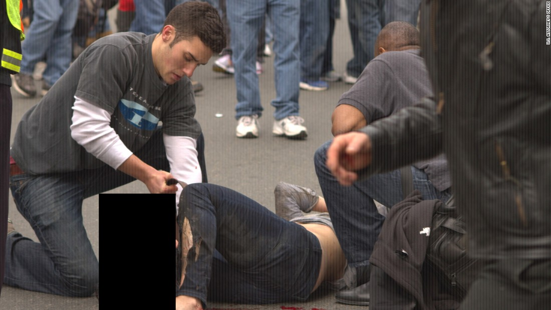 A victim of the Boston Marathon bombing is tended to in the street.