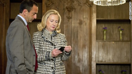 Then-Secretary of State Hillary Clinton looks at a phone message with Assistant Secretary Philip Gordon in 2012.
