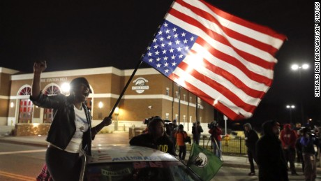 Protesters gather outside Ferguson after the U.S. Justice Department cleared a white former police officer in the fatal shooting of an unarmed black 18-year-old.