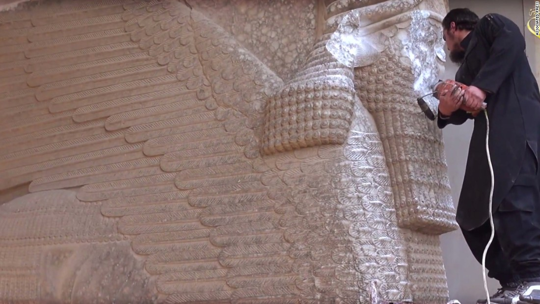 In this image made from video posted on a social media account affiliated with ISIS, a militant uses a power tool to destroy a winged-bull Assyrian protective deity at the Nineveh Museum in Mosul, Iraq.