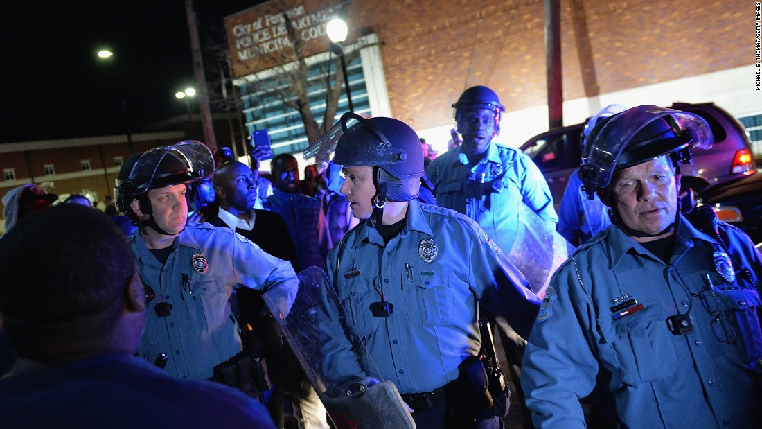 Police in riot gear respond to demonstrators blocking traffic in Ferguson on March 11.