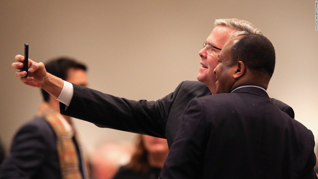 Bush takes a selfie with a guest at a luncheon hosted by the Chicago Council on Global Affairs on February 18, 2015, in Chicago. Bush delivered his first major foreign policy speech at the event.