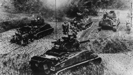 American tanks and infantrymen advance under Japanese attack during the Battle of Okinawa.