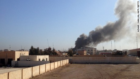 Caption:A picture taken on March 11, 2015 shows smoke billowing after the building of the Anbar Governorate was hit by a mortar shell in the Hosh district of Ramadi as the Islamic State jihadist group launched a coordinated attack on government-held areas of the western Iraqi city, involving seven almost simultaneous suicide car bombs, police said. At least 10 people were killed and 30 wounded in the attack, according to initial reports by police and hospital sources in the city, capital of Anbar province. AFP PHOTO / AZHAR SHALLAL (Photo credit should read AZHAR SHALLAL/AFP/Getty Images)