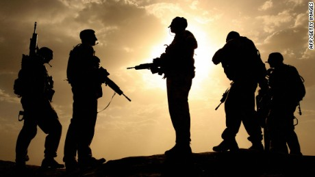 In May 2006, British soldiers are silhouetted against the sky as they provide security in Lashkar Gah, Helmand province.