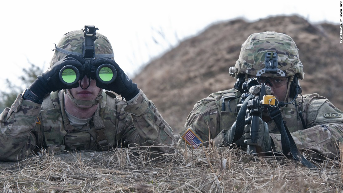 U.S. Army Pfc. William Chaput, left, and Staff Sgt. Demarcus Credit, both of Lightning Troop, 3rd Squadron, 2nd Cavalry Regiment, scan for enemy activity during a combined training exercise at Pabrades training area, March 4, 2015.