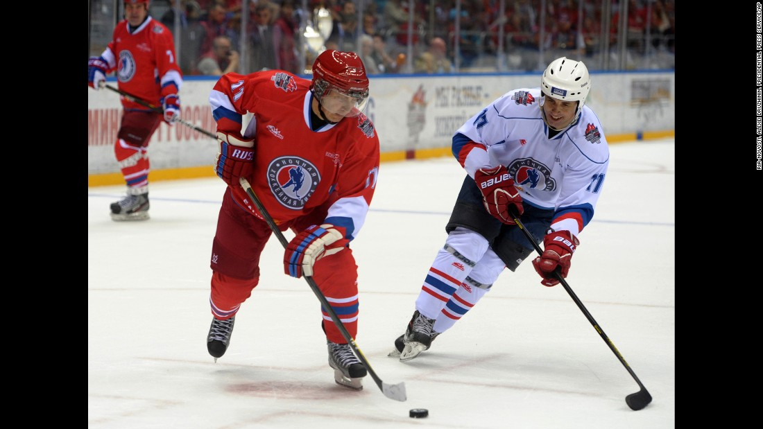 Putin, left, controls the puck during an ice hockey game between Russian amateur players and ice hockey stars at a festival in Sochi in May 2014.