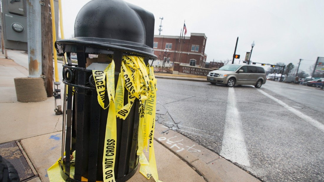 Crime scene tape used to secure the area after two officers were shot outside the Ferguson police station, sits in a trash can on March 13.