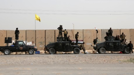 Iraqi security forces and allied Shiite militiamen gather at the front line in Tikrit, Iraq, on Friday, March 13.