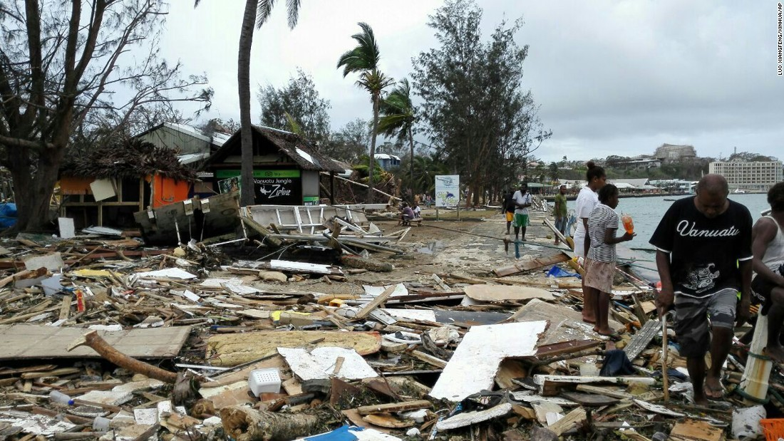 Locals walk past debris in Port Vila on March 15.