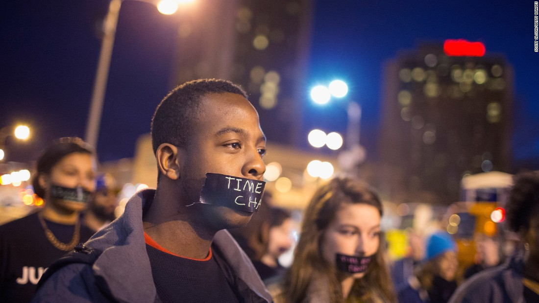 A protester with a taped mouth marches through downtown St. Louis on March 14.