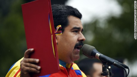 Venezuelan President Nicolas Maduro speaks whilst holding the folder with the decree powers law, in Caracas on March 15, 2015. Venezuela's National Assembly voted Sunday to give President Nicholas Maduro decree-making powers in defense and security affairs amid an escalating confrontation with Washington. The special powers were approved by a show of hands in the assembly after two hours of debate and will be in effect for six months.