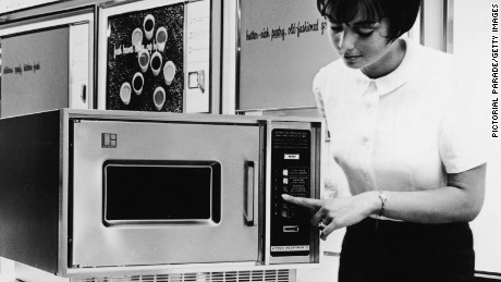 A woman demonstrates a Litton Series 500 microwave oven on a display stand, circa 1966. (Photo by Pictorial Parade/Getty Images)