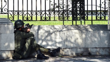 A security member holds his position near the Bardo Museum.