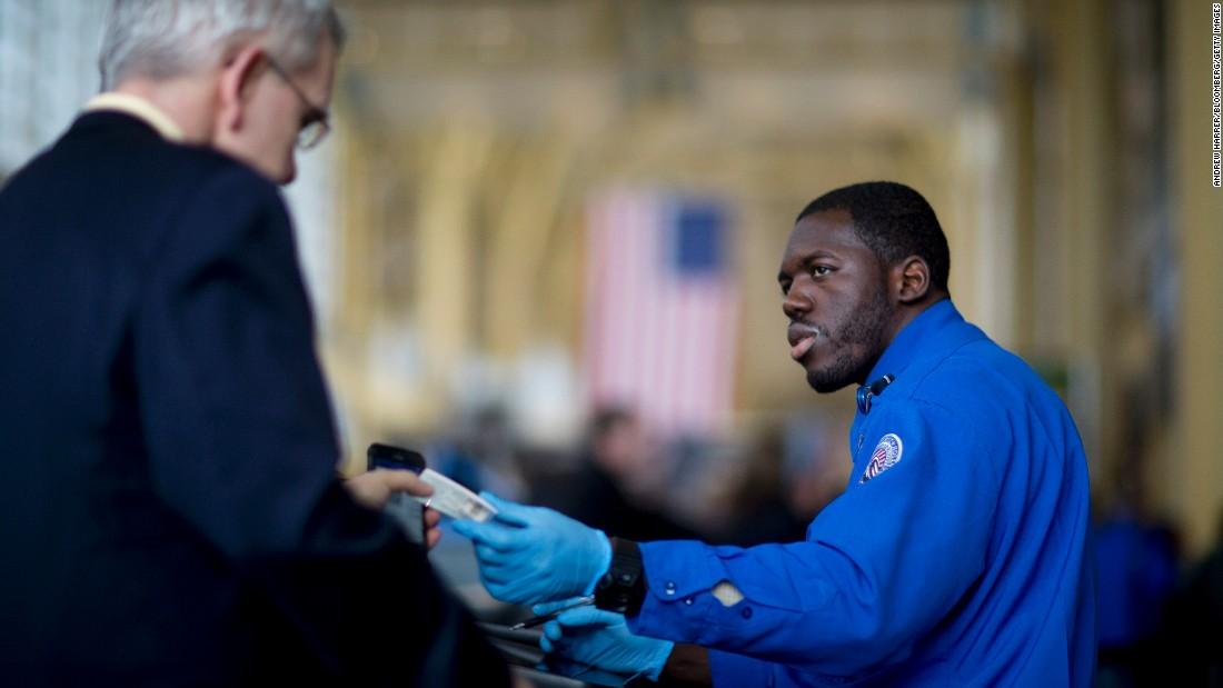 A TSA officer hands a passenger his identification at a security checkpoint at Ronald Reagan National Airport in Washington.