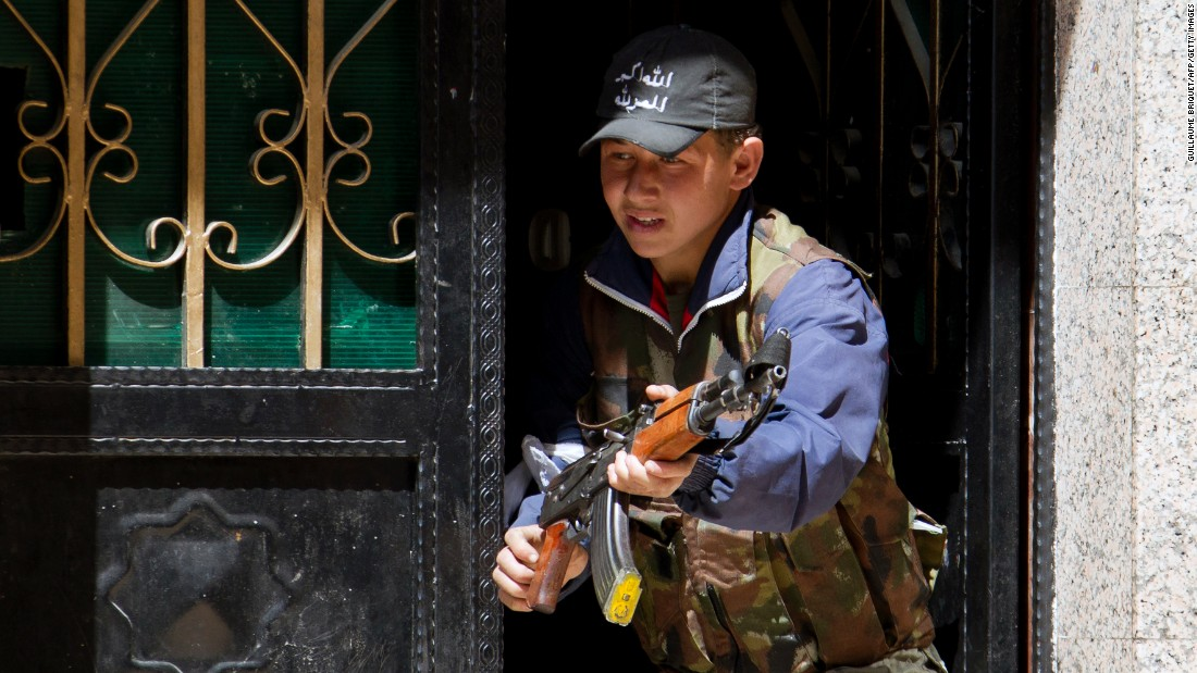 A young rebel fighter holds a weapon at the entrance of a house in the Syrian city of Aleppo in March 2013.