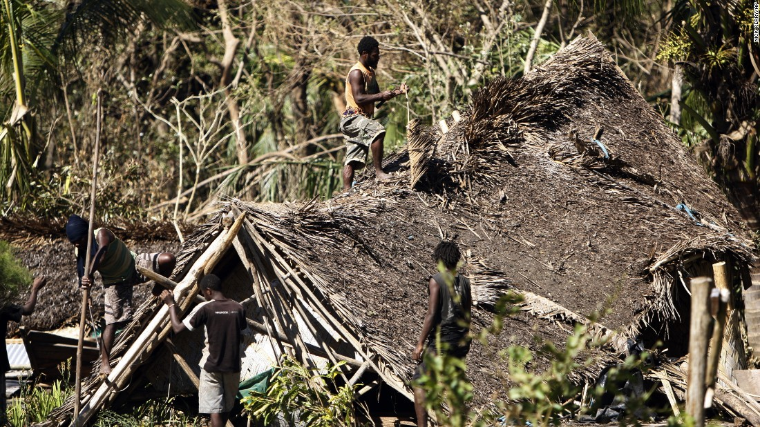Young men take apart a damaged hut on March 19 on Tanna Island.