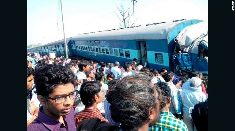 A crowd watches as emergency workers help victims of a passenger train derailment in India's Uttar Pradesh state on Friday.