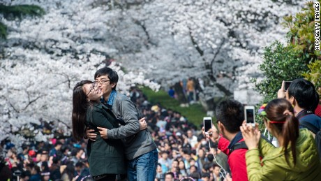 This picture taken on March 21, 2015 shows a couple posing in front of blooming cherry blossoms in Wuhan in central China's Hubei province. The cherry blossoms, now in full bloom, attracted tens of thousands of visitors, local media reported. CHINA OUT AFP PHOTOSTR/AFP/Getty Images