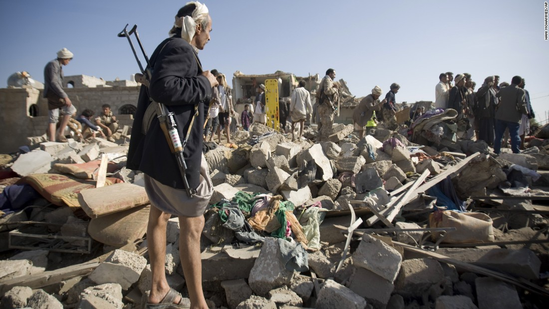 A Houthi fighter stands guard March 26 as people search for survivors under the rubble of houses destroyed by airstrikes near the Sanaa Airport.