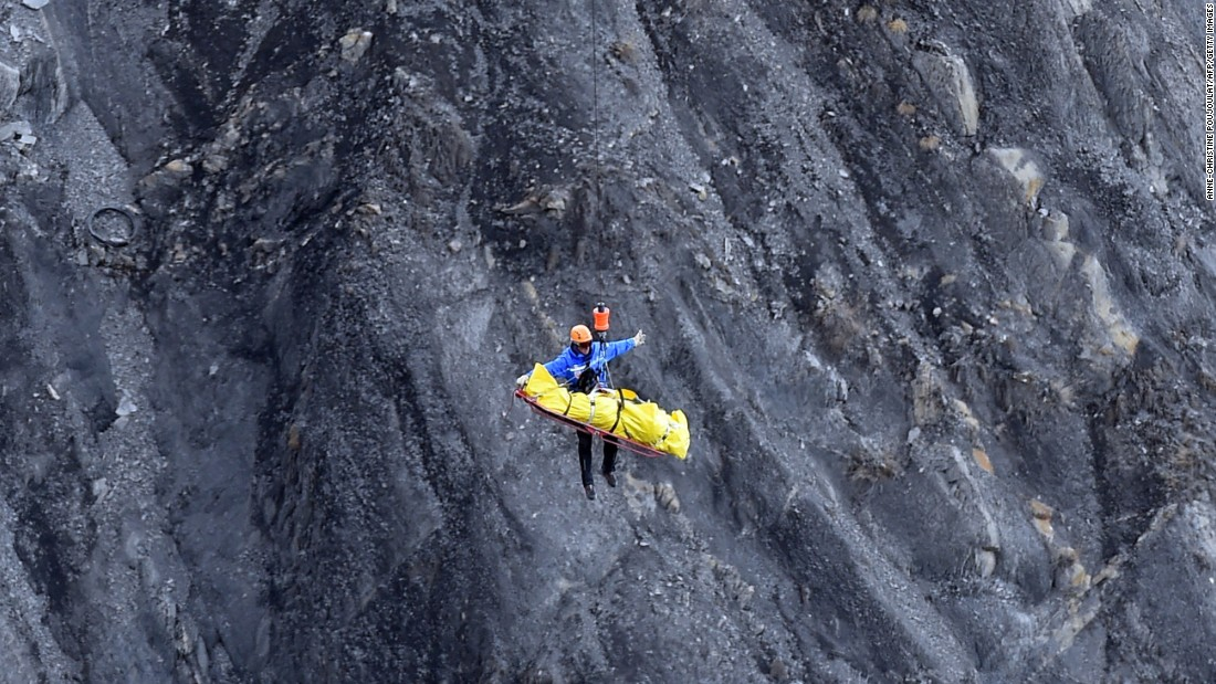 A helicopter lifts a rescue worker from the crash site in the French Alps on March 26.