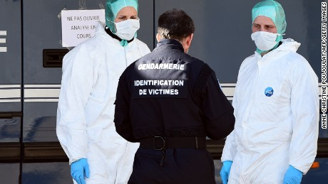 Police officers stand outside a mobile laboratory where the DNA samples of victims of the Germanwings air crash are being tested in Seyne-les-Alpes on March 27, 2015.