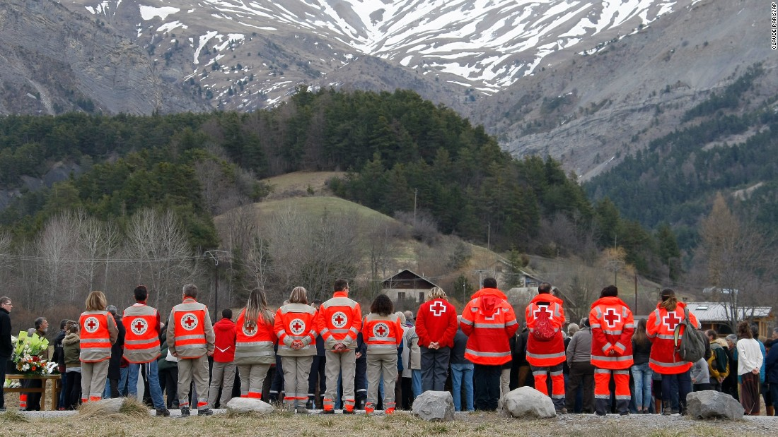 French Red Cross members and residents pay tribute to the victims in front of a stele, a stone slab erected as a monument, near the site of the crash near Le Vernet on Saturday, March 28. The crash of Germanwings Flight 9525 into an Alpine mountain, killing all 150 people aboard, has raised questions about the mental state of the co-pilot.
