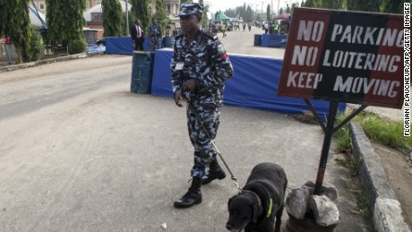 A police officer uses a dog to sweep the area before the arrival of incumbent Nigerian president to cast his ballot during presidential elections at polling station in Otuoke on March 28, 2015. Voting began in Nigeria's general election but delays were reported countrywide because of technical problems in accrediting electors.