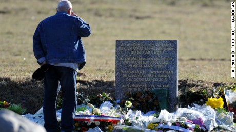 A man stands on March 29 2015 in front of a commemorative headstone in Seyne-les-Alpes, the closest accessible site to where a Germanwings Airbus A320 crashed on March 24 in the French Alps, killing all 150 people on board.