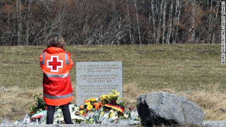 A  Red Cross member pays tribute for the victims of the Germanwings plane crash in front of a memorial in Le Vernet on March 27, 2015. The Germanwings co-pilot who crashed his Airbus into the French Alps, killing all 150 aboard, hid a serious illness from the airline, prosecutors said amid reports he was severely depressed. AFP PHOTO / BORIS HORVAT (Photo credit should read BORIS HORVAT/AFP/Getty Images)