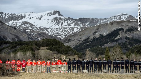 French rescue workers gather in front of a memorial for the victims of the Germanwings air crash in Le Vernet, southeastern France, on March 28, 2015. The Germanwings co-pilot who crashed his Airbus into the French Alps, killing all 150 aboard, hid a serious illness from the airline, prosecutors said amid reports he was severely depressed. AFP PHOTO / JEFF PACHOUD (Photo credit should read JEFF PACHOUD/AFP/Getty Images)