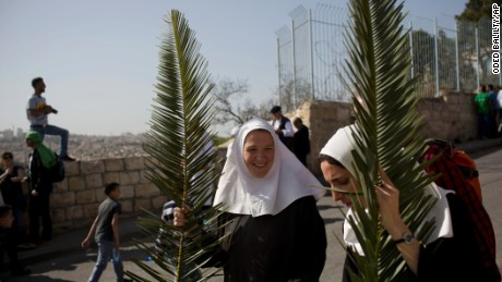 Christian nuns hold palm fronds during a Palm Sunday procession on the Mount of Olives overlooking Jerusalem's old city.