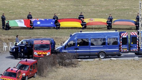 Gendarmes hold flags of the victims' countries as relatives of the victims of the crash of a Germanwings Airbus A320 arrive at a funary stele set in Seyne-les-Alpes, the closest accessible site of the crash, on March 30 2015. A German airliner crashed near a ski resort in the French Alps on March 24, killing all 150 people on board, in the worst plane disaster in mainland France in four decades.
