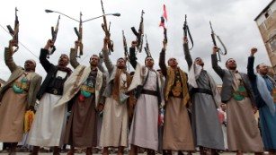 Houthi fighters raise their weapons
