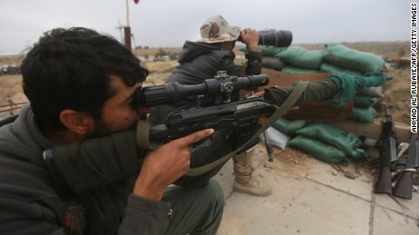 :Iraqi government forces keep watch from a position on the southern outskirts of Tikrit, on March 30, 2015, during a military operation to retake the city from Islamic State (IS) group jihadists. Retaking Tikrit, where jihadists have rigged streets and buildings with explosives, will require 'major sacrifices' on the part of Iraqi forces, a senior intelligence officer said