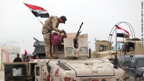 A member of the Iraqi security forces stands atop a military vehicle outside the western entrance of the city of Tikrit on March 28, 2015 during a military operation to retake the northern Iraqi city from Islamic State group jihadists