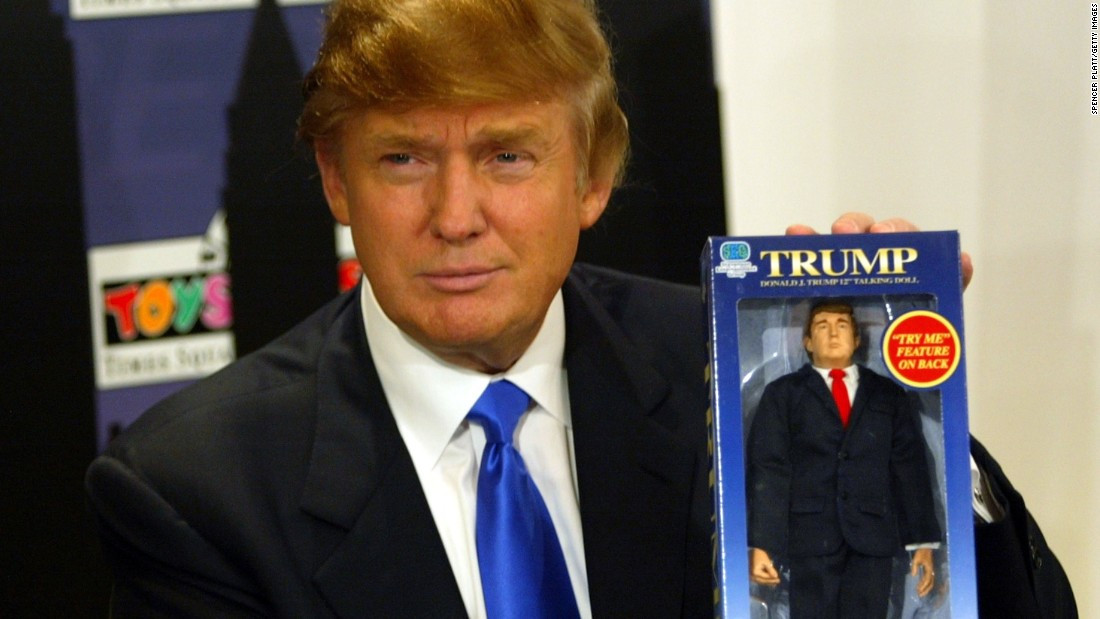 Trump poses with the new Donald Trump 12-inch talking doll September 29, 2004, at the Toys 'R' Us store in New York City.