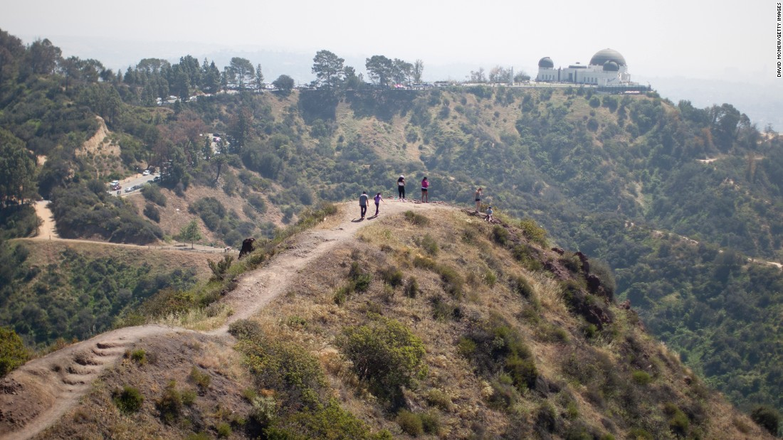 People hike along a ridge overlooking the Griffith Observatory, where vegetation is quickly drying out in Los Angeles on Sunday, March 29.