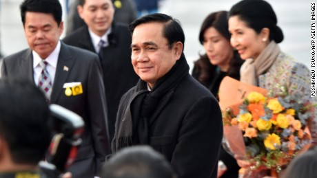 Thai Prime Minister Prayut Chan-O-Cha (C), accompanied by his wife Naraporn (R), arrives at Tokyo International Airport on February 8, 2015. Prayut is on a three-day visit to Japan. AFP PHOTO / Yoshikazu TSUNO (Photo credit should read YOSHIKAZU TSUNO/AFP/Getty Images)