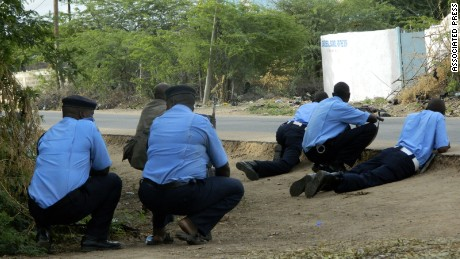 Kenyan police officers take cover outside the Garissa University College during an attack by gunmen in Garissa, Kenya, Thursday, April 2, 2015. Gunmen attacked the university early Thursday, shooting indiscriminately in campus hostels. Police and military surrounded the buildings and were trying to secure the area in eastern Kenya, police officer Musa Yego said. (AP Photo)