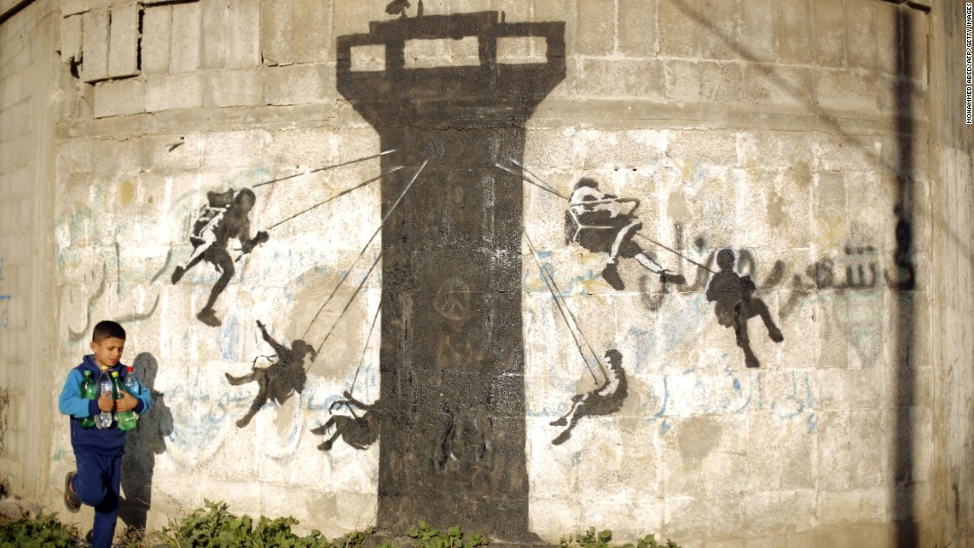A child in Beit Hanoun walks past a mural February 2015 that depicts children using an Israeli watchtower as a swing ride.