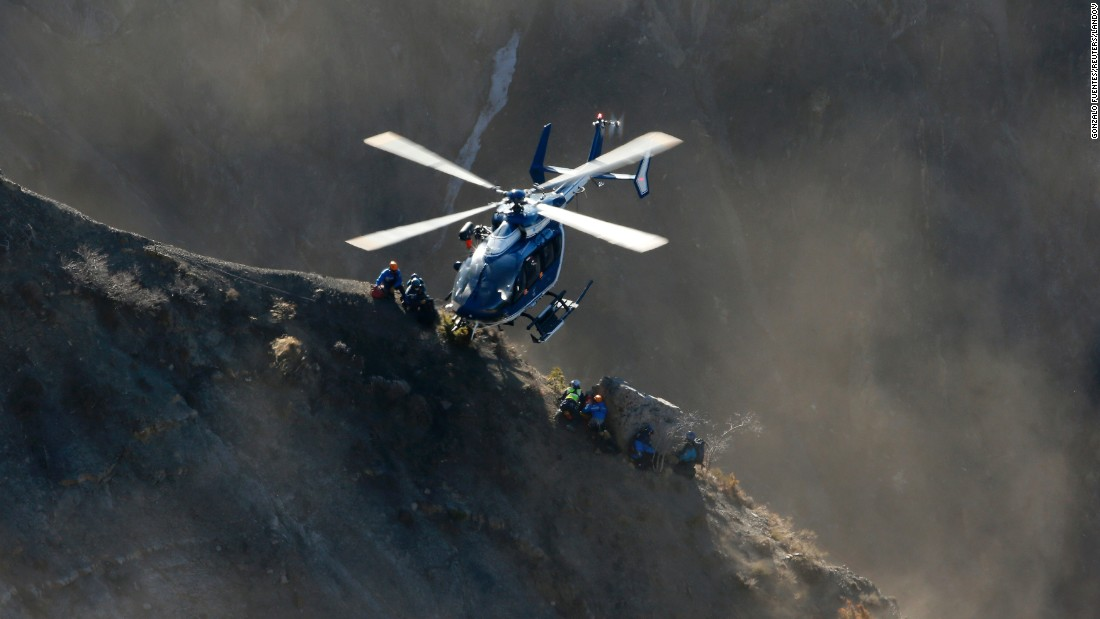 A helicopter drops rescue workers next to crash debris near Seyne-les-Alpes, France, on Sunday, March 29.