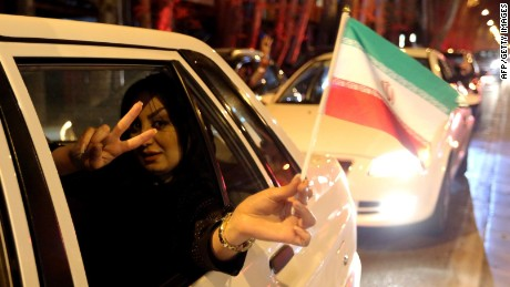 """A woman in a car flashes the """"V for Victory"""" sign and waves an Iranian flag as people celebrate on Valiasr street in northern Tehran on April 2, 2015, after the announcement of an agreement on Iran nuclear talks. Iran and global powers sealed a deal on April 2 on plans to curb Tehran's chances for getting a nuclear bomb, laying the ground for a new relationship between the Islamic republic and the West. AFP PHOTO / ATTA KENAREATTA KENARE/AFP/Getty Images"""